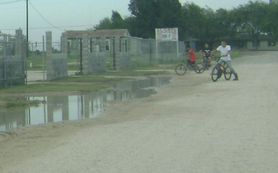 Agua estanca en una colonia mientras niños juegan cerca.