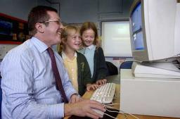 Mark with pupils in their new IT suite (photo courtesy of Stockport Express)