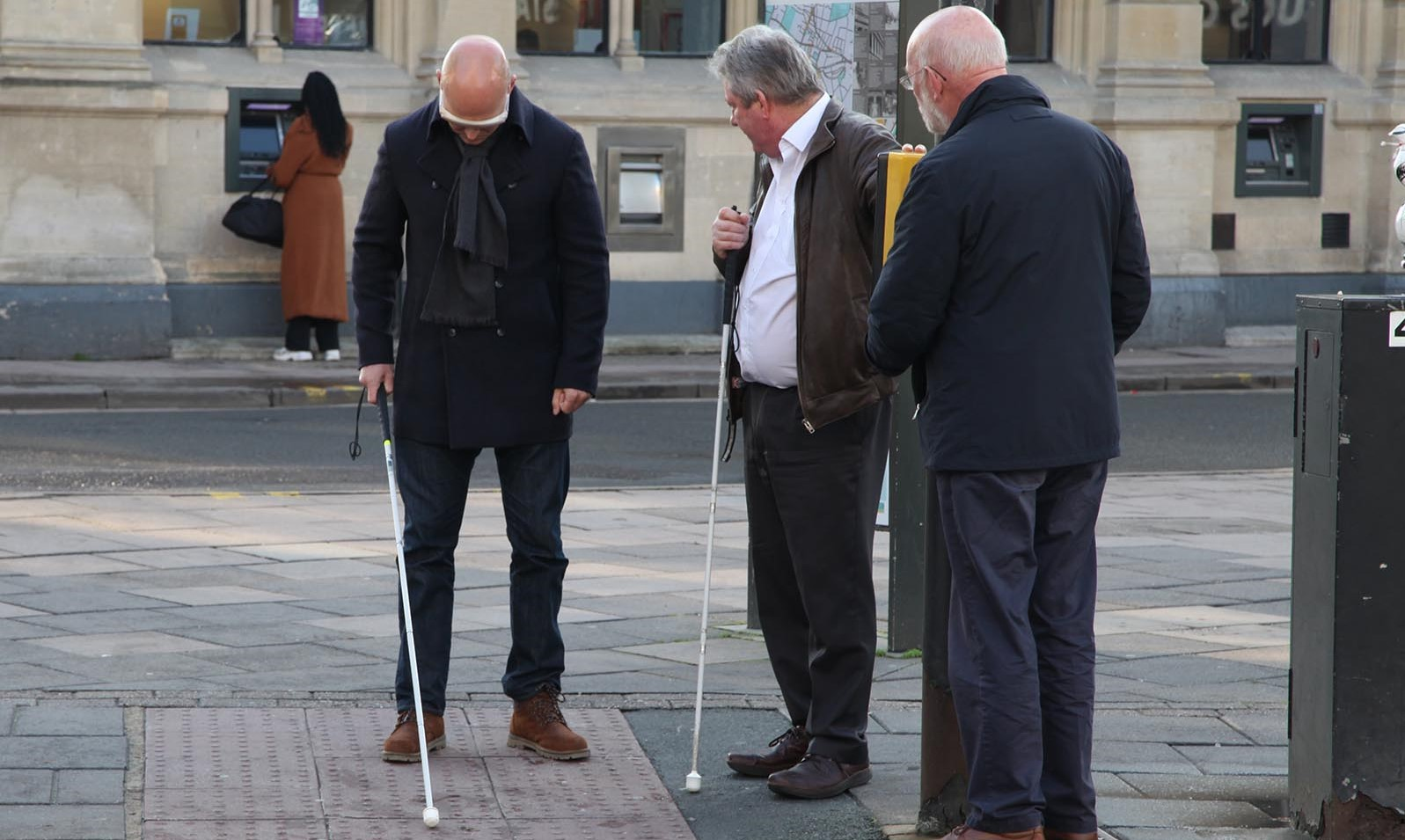 Max Wilkinson on a Cheltenham street using a white cane and a blindfold with RNIB campaigners