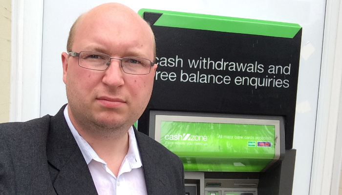 Activist Ben Mathis with a fee-charging ATM in Hackney Wick