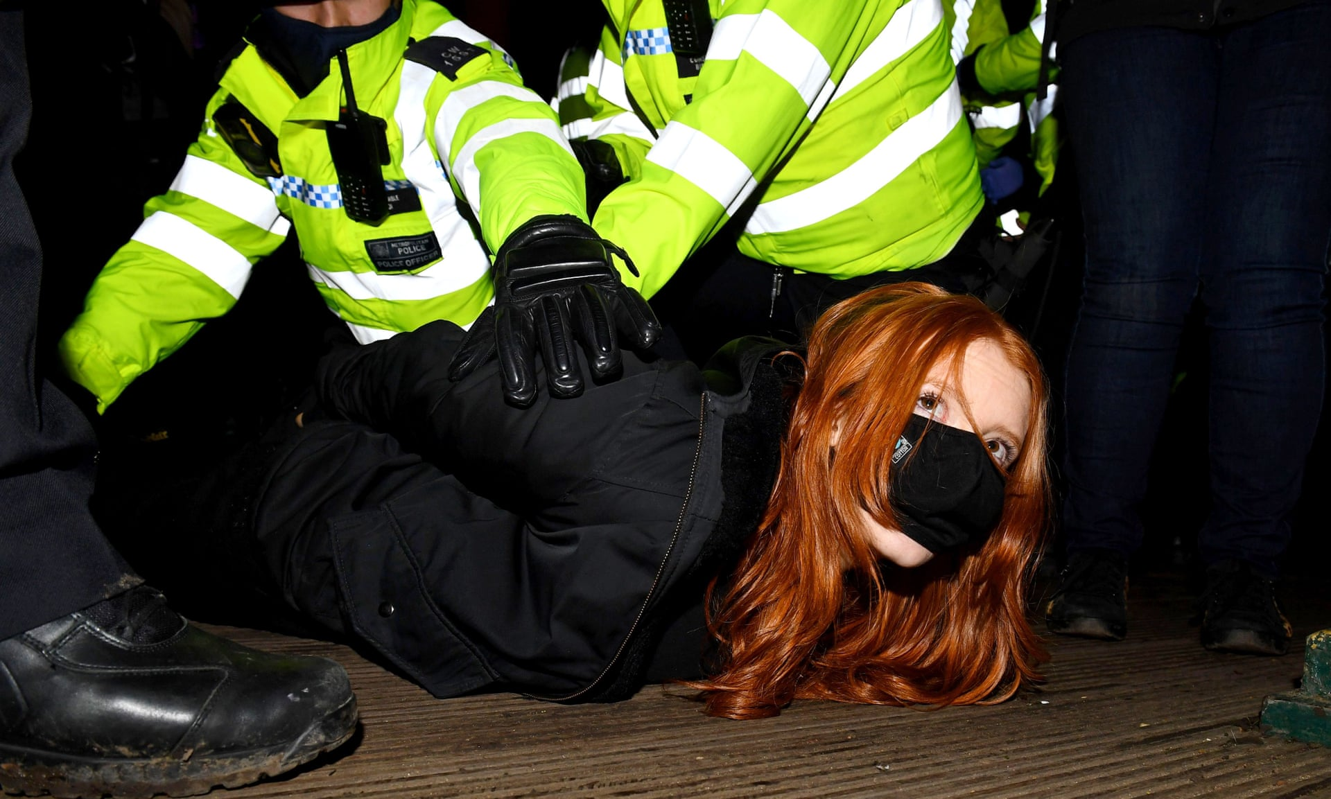 Patsy Stevenson, a young woman, on the ground being arrested by police who have their knees on her