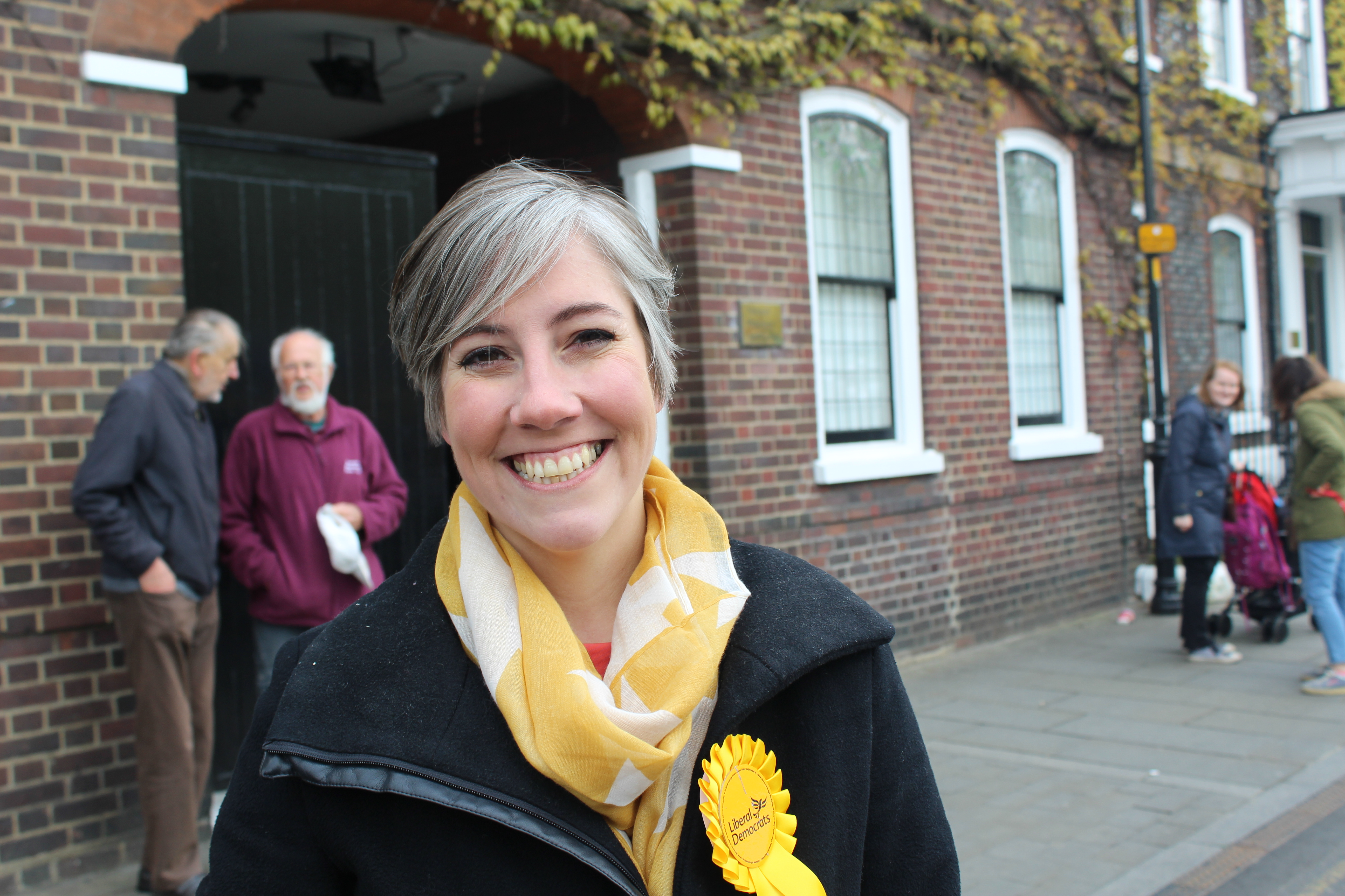 Image of Daisy Cooper smiling with background of a street on a sunny day