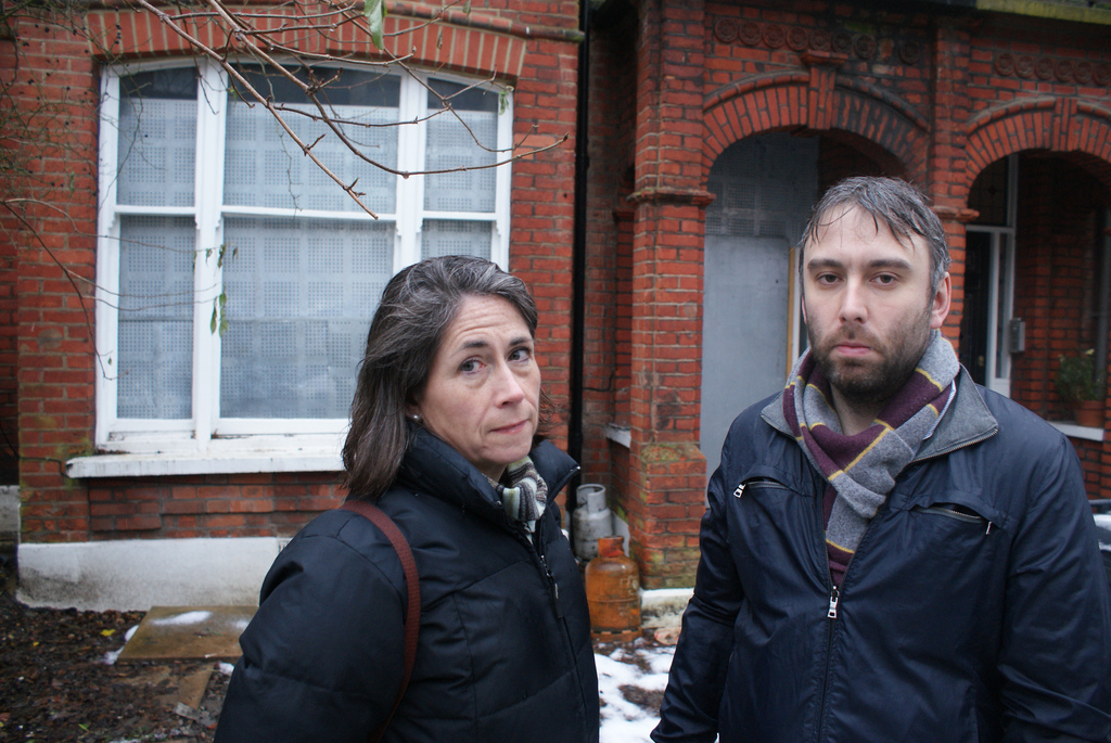 Lib Dem campaigners outside a boarded up empty home