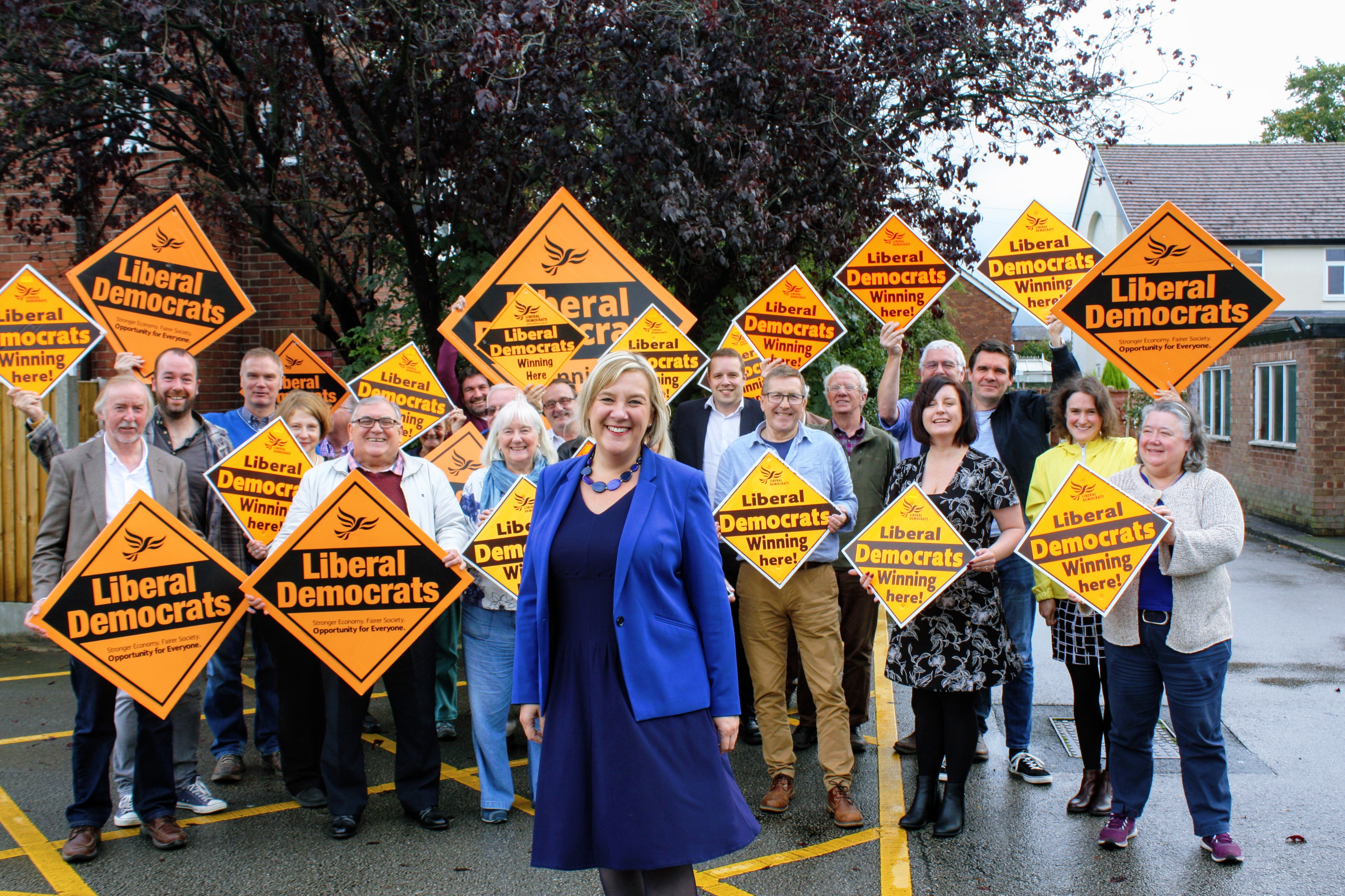 Lisa Smart surrounded by a crowd of Hazel Grove Liberal Democrats holding Lib Dem diamond signs