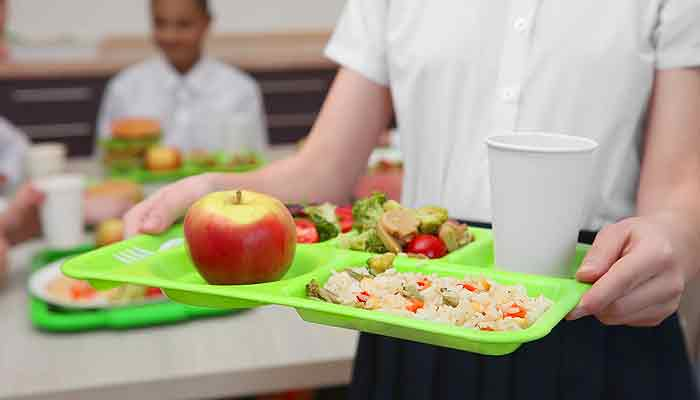 Image of child carrying school meal tray.