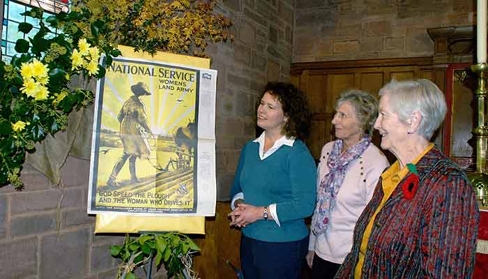 Kirsten Johnson, with Mary Lethbridge (Organiser) and Margaret Bannister view a flower arrangment featureing a poster for the Women's Land Army