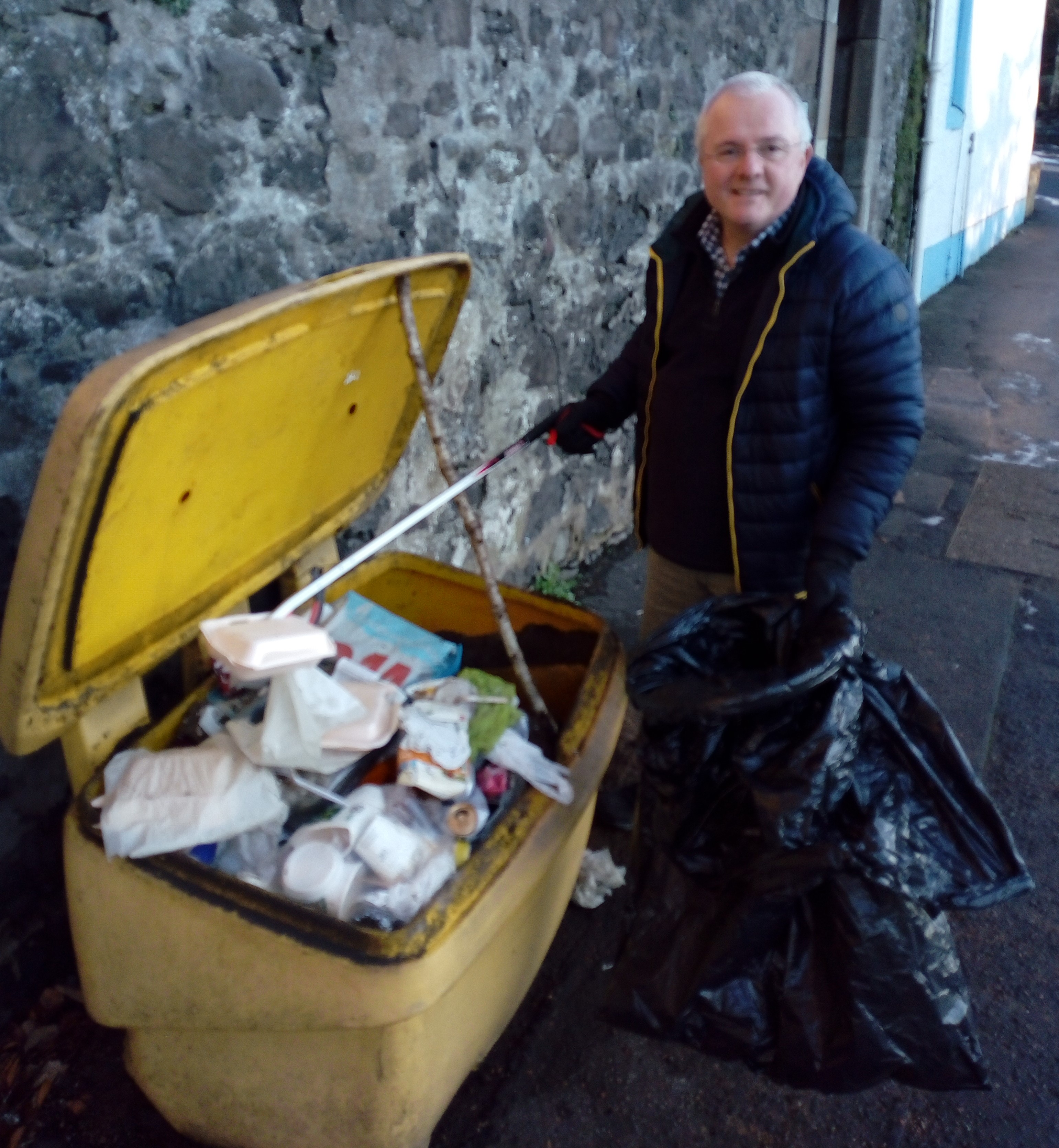 Cllr Barrett clears rubbish from a grit-bin so residents can get at the salt to treat their area.