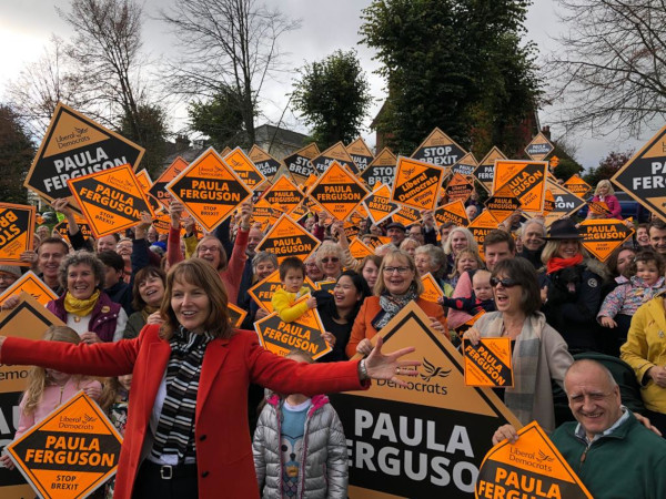 Liberal Democrat candidate Paula Ferguson standing in front of a large group of brightly coloured excited supporters at her General Election Campaign Launch