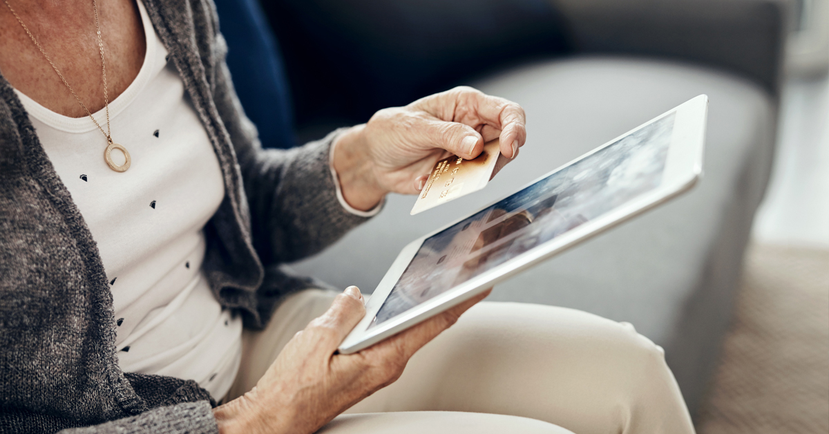 Older women uses a credit card with her ipad.