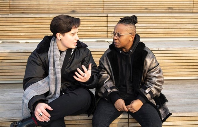 Two lesbians sit on stone steps and talk privately.