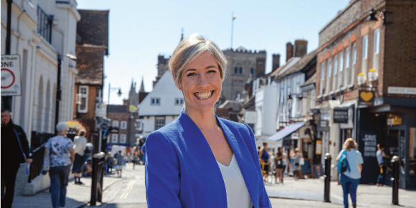 Daisy Cooper smiles at the camera, pictured on a high street