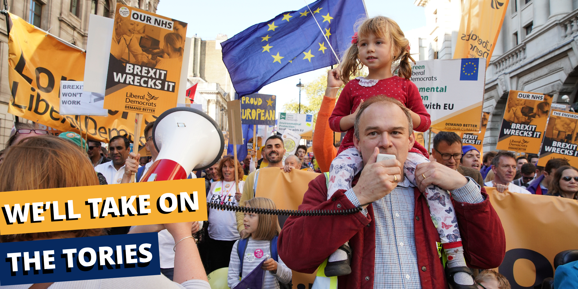 Ed Davey holding a megaphone in front of a large crowd of Lib Dems. Banner from left reads 'We'll take on the Tories