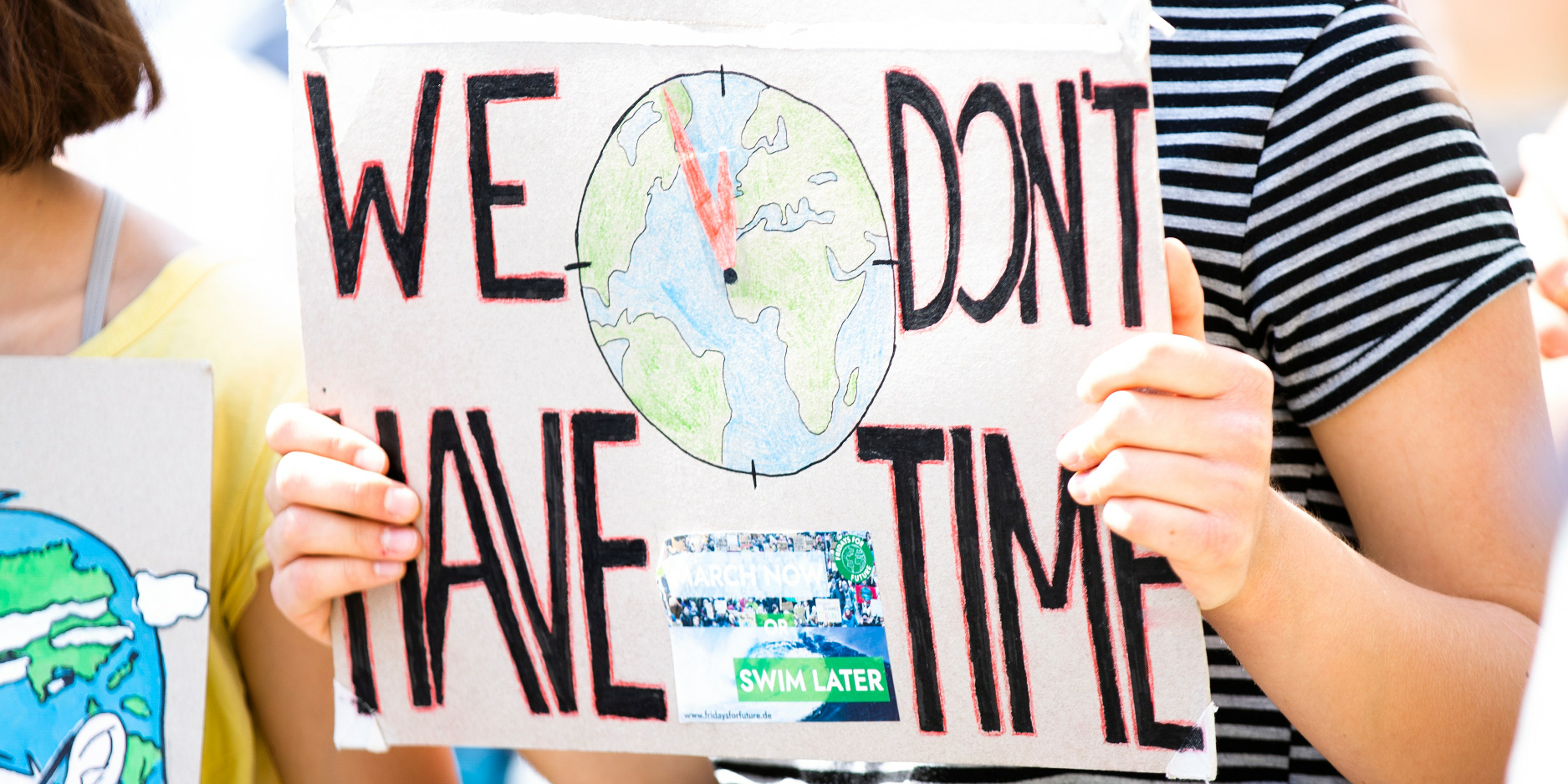 Child holding sign saying 'We Don't Have Time'