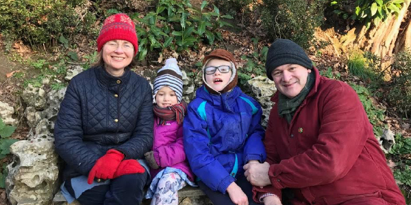 Ed, his wife and two children smiling, wearing coats in a leafy green area.
