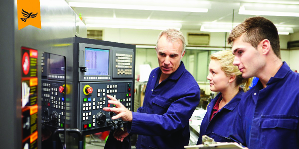 2 apprentices are shown something on a screen. They wear boiler suits.