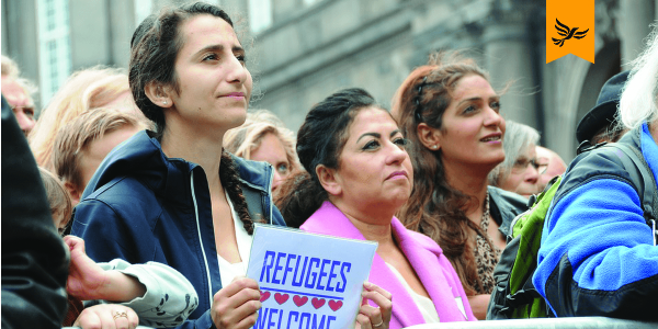 A group at a protest, one holding a sign saying 'refugees welcome'