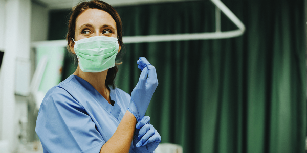 A medical professional wears a mask and gloves