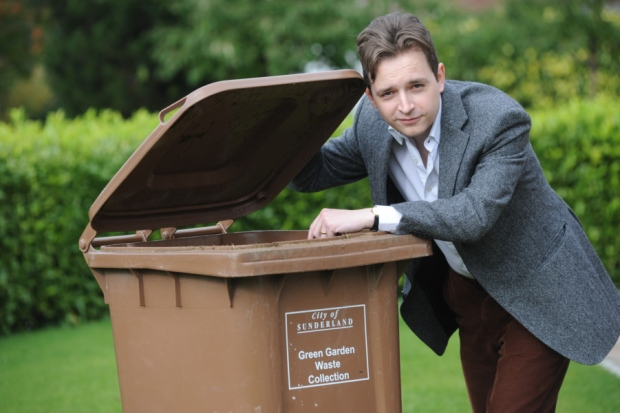 Lib Dem councillor Niall Hodson posing leaning on a brown bin