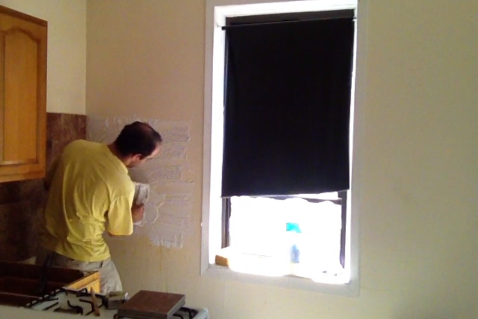 Daniel rehabs an apartment for his non-union employer, adding adhesive to a kitchen wall in preparation for installing a tile backsplash. (Courtesy of Daniel)