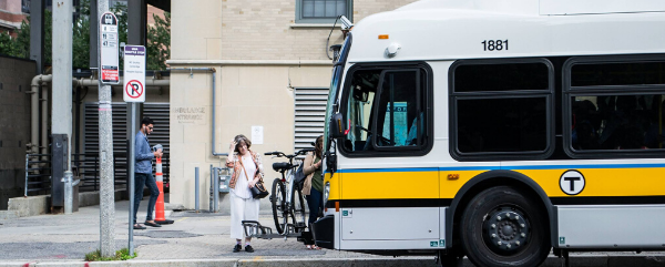An MBTA bus stops at a bus stop; some people board the bus; there is also a bicycle attached to the front