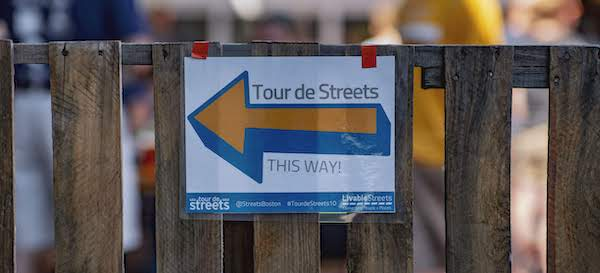 A Tour de Streets sign with an arrow pointing left is attached to a wooden fence.
