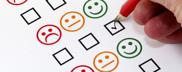 A page with emojis: a red frowning face, a yellow face with a straight-line mouth, and a green smiling face; below each row of emoji is a row of checkboxes. A hand holding a pen checks off a checkbox under a smiling emoji.