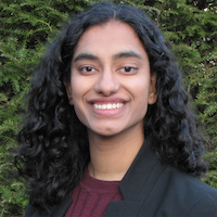 Archana, a woman of South Asian descent with curly black hair, smiles at the camera in front of pine trees.