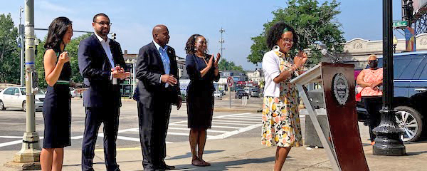 Mayor Kim Janey stands on a sidewalk behind a podium and applauds, smiling; she wears a yellow floral dress and a white cardigan. Behind her stand four Boston city councilors, who are also smiling and applauding; in the background is an intersection with a pedestrian crosswalk.