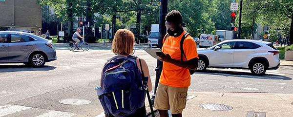 Moctar, a young Black man in an orange LivableStreets tshirt, khaki shorts, and a black face mask, stands holding a clipboard. In front of him is a short white woman with chin-length light brown hair; her back is to the camera as she looks at him, and we can see her blue backpack. The background is part of Mass Ave near Kendall Sq, with trees on the other side and cars and a cyclist going by.