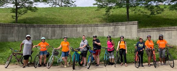 A group of people, about half of whom are wearing orange LivableStreets tshirts, stand in a line holding their bicycles. Everyone is smiling at the camera, and most are wearing bicycle helmets. The background is a grassy hill with a decorative concrete retaining wall; there are trees and blue sky cut off at the top of the photo.