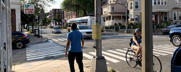 A view of the intersectino of Highland Ave and School Street. A man approaches a crosswalk; a woman rides past on her bicycle, and cars and a bus drive through the intersection.