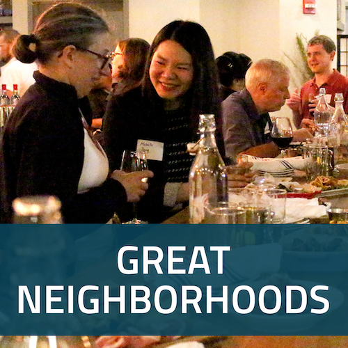 A square button with a picture of people enjoying a T or Drinks event, with the words Great Neighborhoods in white on a dark blue background