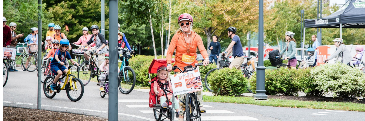 three people riding bicycles along a tree-lined path. the woman at the front of the line is wearing an orange sweater and has a child seat on her bicycle with a small child in it