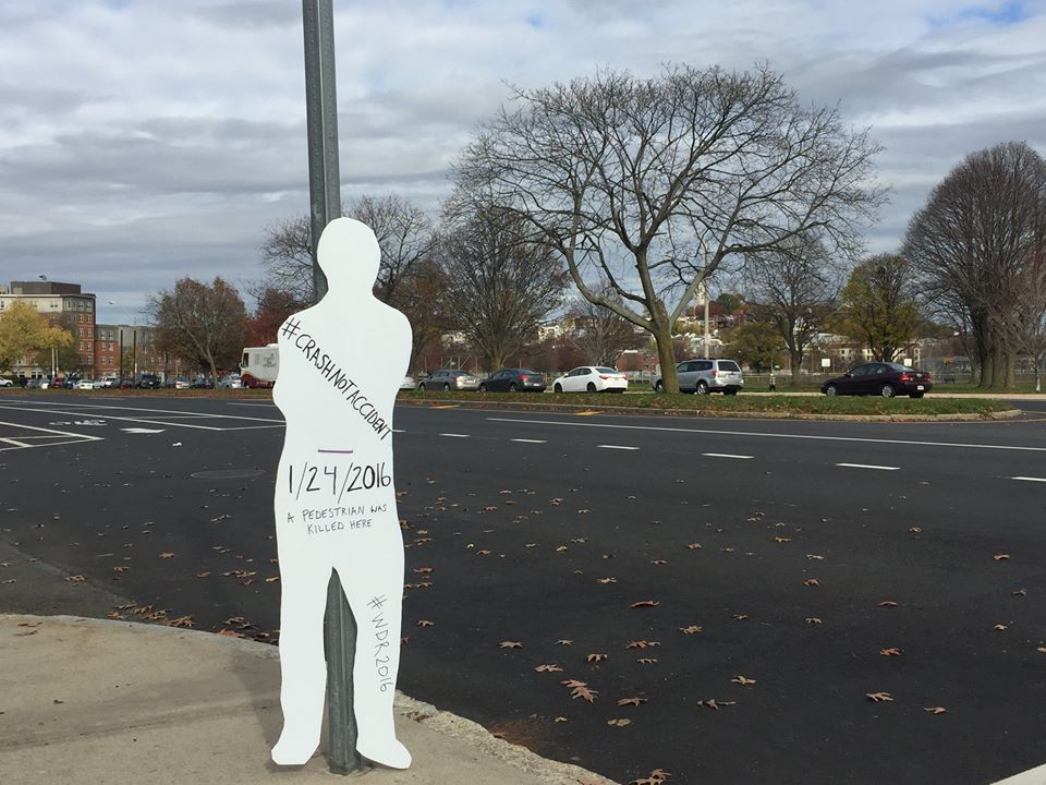 """A white cardboard sillhouette with the words """"#crashnotaccident"""" and the date 1/24/2016, indicated as the date of the pedestrian's death from a traffic crash leans against a telephone pole. In the background is a large road with several lanes."""