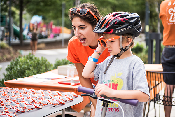 A white woman with brown hair and a child in a bicycle helmet look at a table on which sit a large number of orange sunglasses.