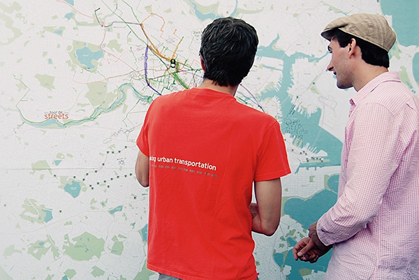 Two people look at a map of the Boston area.
