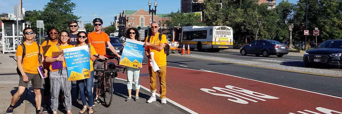 """A group of people in LivableStreets orange shirts stand on the side of a road next to a bus-bike lane. They are smiling at the camera while holding signs that say things like """"I (heart) Allston's New Bus-Bike Lanes; Thank you MBTA and Mayor Walsh"""""""