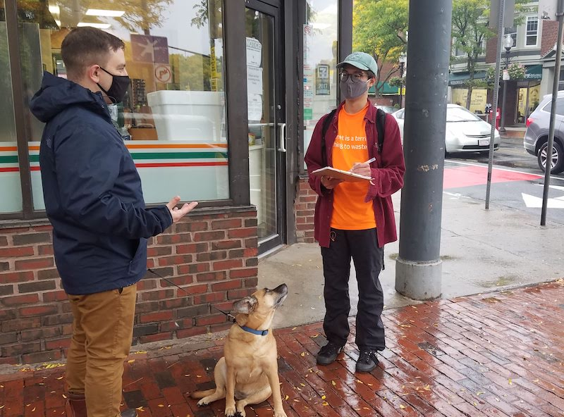 Two men with light skin talk while standing on a corner next to a storefront. They are both wearing masks, and one is a Street Ambassador in an orange LivableStreet shirt. The other man holds the leash of a dog who looks up in curiosity at the Street Ambassador.