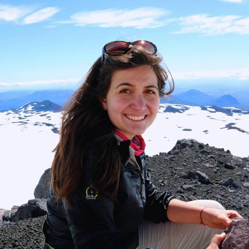 María de la Luz, a young Latinx woman with long brown hair, looks at the camera with a smile as she crouches in front of a snowy mountain scene.