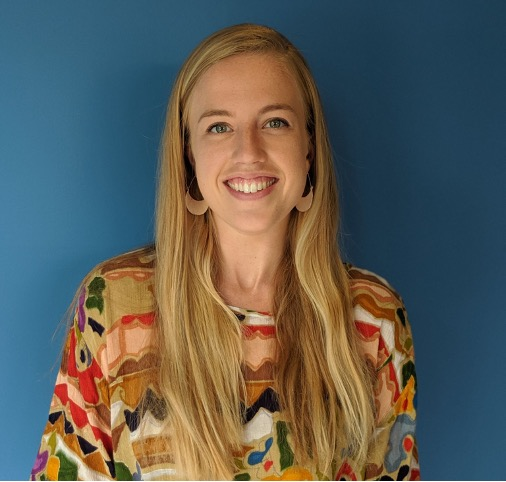Kelsey, a white woman with long blonde hair and a colorful shirt, smiling in front of a blue background.