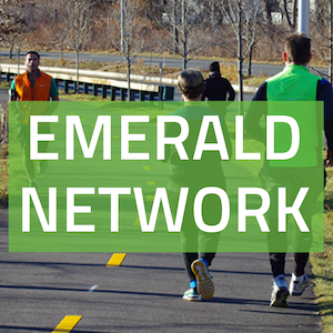 "A square button with a picture of people jogging on a bike path, with the words ""Emerald Network"" written on a green background"