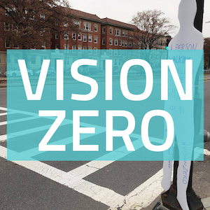 "A square button with a photo of a person-shaped cardboard cutout on one side of a crosswalk, with the words ""Vision Zero"" on a blue background"