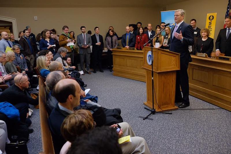 A grey-haired white man in a suit stands behind a podium and addresses citizens, journalists, and government officials who are seated in rows in front of him and standing against the walls surrounding him.
