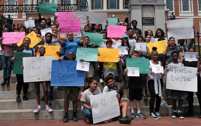A crowd of high school students of color stand on the State House steps, holding signs with slogans against texting while driving.