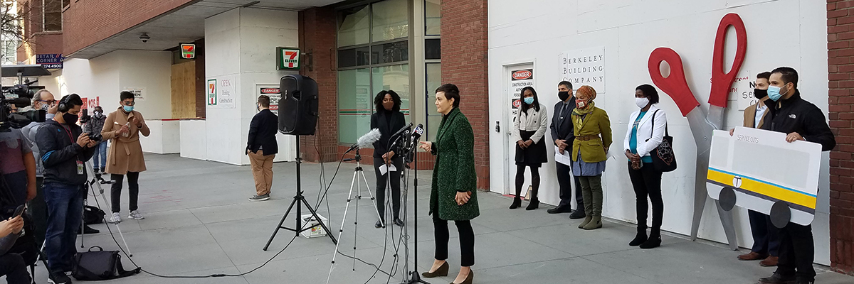 A photo banner of a press conference. LivableStreets executive director Stacy Thompson stands in front of a few microphones; at least six feet behind her, in a line, stand several people wearing masks. One holds a cardboard facsimile of an MBTA bus, and giant scissors around 8 feet tall lean against the wall of the building behind the line of people. On the left side of the photo is a crowd of reporters, some with cameras.