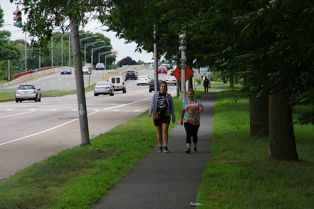 Two people walk down a tree-lined greenway alongside a busy divided road.