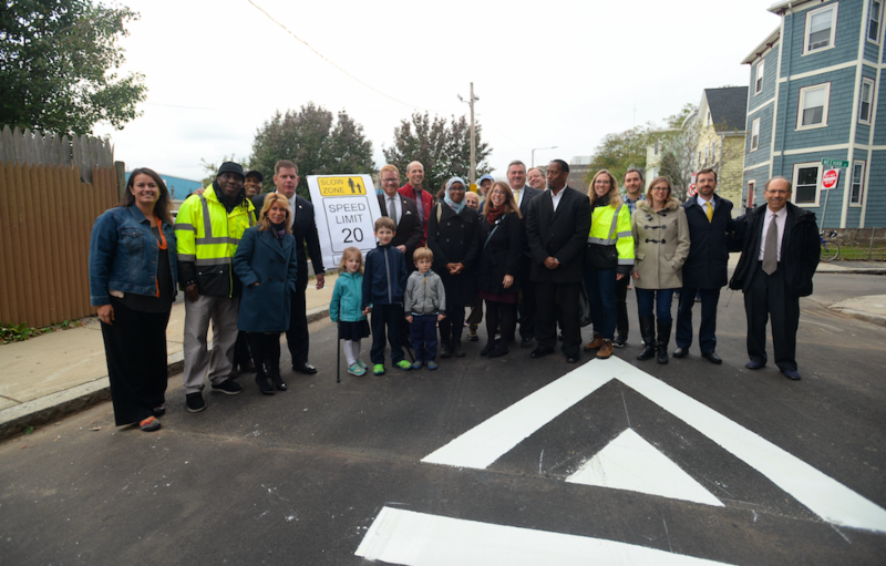 A crowd of people stand by a speed bump, gathered around a sign that calls for 20mph speed limits.