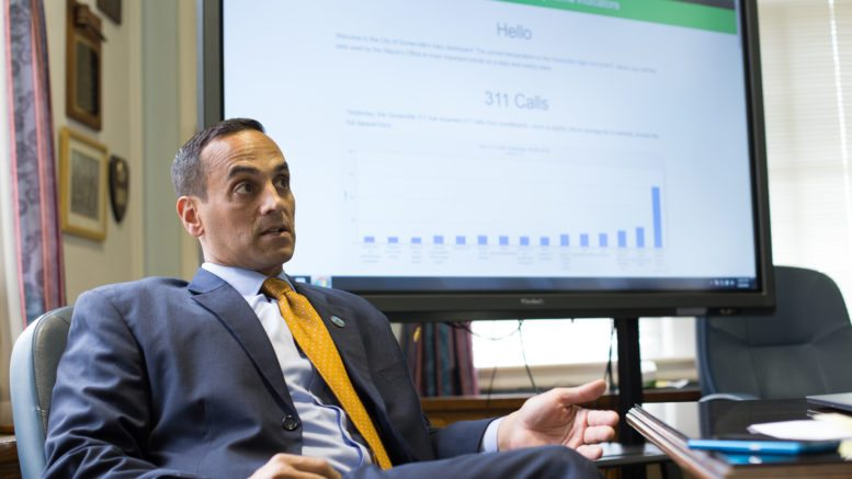 Somerville mayor Joe Curtatone sits in a office chair, looking like he's explaining something. Behind him is a large screen with a chart.
