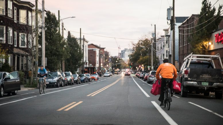A two-way street in Somerville, with parking and bike lanes on both sides. A cyclist approaches on the left side of the road and another one, holding several reusable shopping bags on their handlebars, bikes away from the camera on the right.