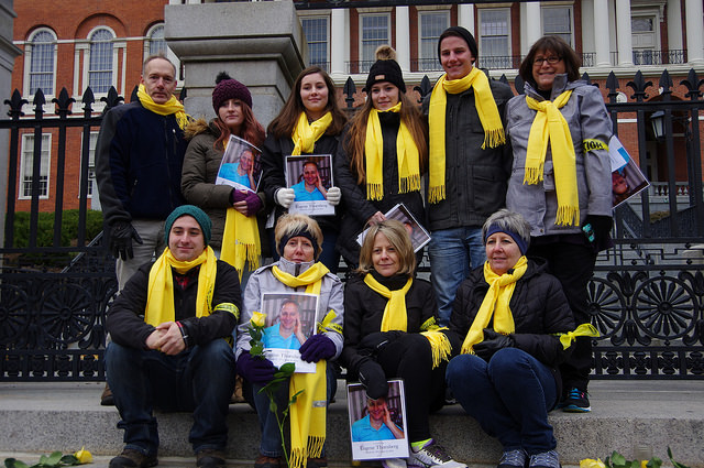 A group of people wearing yellow scarves for World Day of Remembrance are in front of the Massachusetts State House in Boston. One row is sitting on the steps and the other is standing behind them.